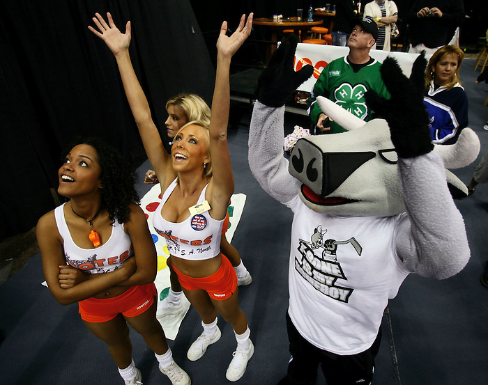 Hooters girls reach for falling stuffed cows with San Antonio Rampage mascot T-Bone during the second period of an AHL hockey game, Saturday, April 11, 2009, in San Antonio, Texas. (Darren Abate/pressphotointl.com)