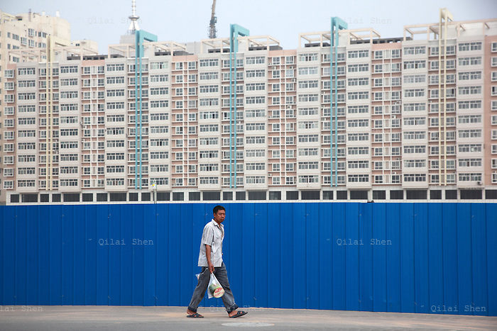 A man walks past a new apartment development on the outskirts of Yulin, Shaanxi Province, China on 14 August, 2011. Like many coal rich regions in China's arid northwest, a vast amount of mineral wealth has been re-invested into the local economy in the form of speculative real estate ventures, creating hundreds of new cities that claims few real residents.