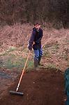 A913JF Young boy raking vegetable garden soil