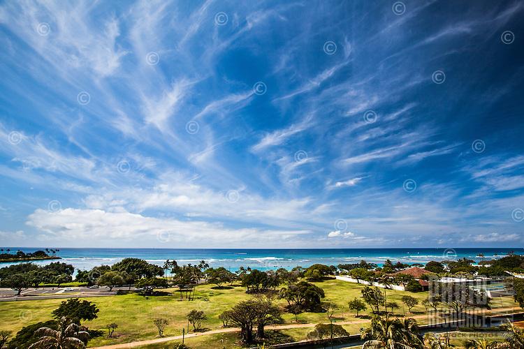 Clouds streak across the sky above Ala Moana Beach Park, with Magic Island on the left, Honolulu, O'ahu.