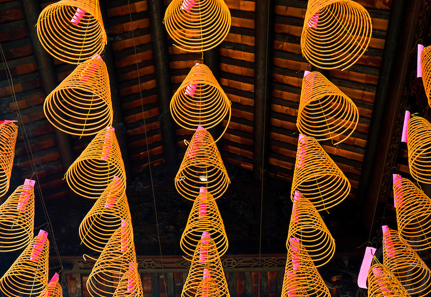 Conical incense coils hanging on wires below the roof at Chua Thien Hau Temple in Cho Lon, Ho Chi Minh City, Vietnam. Thien Hau Pagoda. Cholon, Ho Chi Minh City, Saigon<br /> Ch&ugrave;a B&agrave; Thi&ecirc;n Hậu is a Chinese style temple located on Nguyễn Tr&atilde;i Street in the Cho Lon, District 5 of Ho Chi Minh City, Vietnam. It is dedicated to Thi&ecirc;n Hậu, the Lady of the Sea, who is also known as &quot;Mazu&quot;.