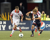D.C. United midfielder Chris Pontius (13) brings the ball forward as New England Revolution midfielder Scott Caldwell (6) closes. In a Major League Soccer (MLS) match, the New England Revolution (blue) tied D.C. United (white), 0-0, at Gillette Stadium on June 8, 2013.