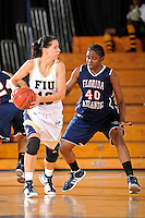 21 January 2012:  FIU guard Fanni Hutlassa (10) handles the ball while being defended by FAU guard-forward April Goins (40) in the first half as the Florida Atlantic University Owls defeated the FIU Golden Panthers, 50-49, at the U.S. Century Bank Arena in Miami, Florida.