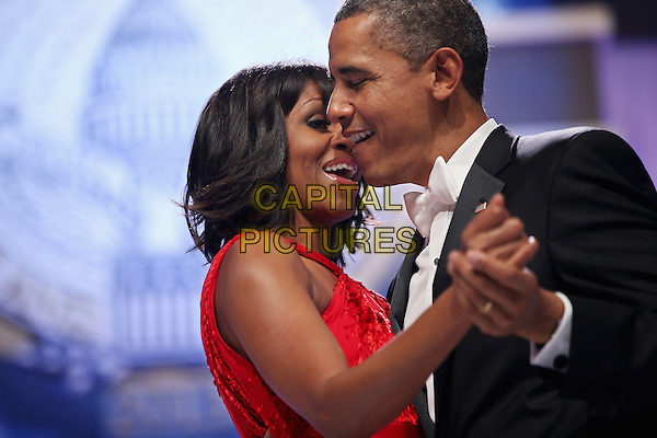 Michelle Obama & Barack Obama.2013 Inauguration Ball, Washinton D.C., USA..January 21st, 2013.half length black suit tuxedo red dress profile holding hands married husband wife dance dancing    .CAP/ADM/CNP/CS.©Chip Somodevilla/CNP/AdMedia/Capital Pictures