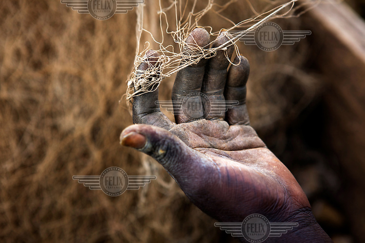 The hand of a young fisherman repairing his nets at Ggaba landing site on the shore of Lake Victoria in Kampala.