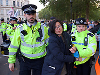 Environmental activists from Extinction Rebellion protesters being arrested after being cut free and un-glued in London on 09 October 2019 in London, England.<br /> .<br /> Protesters plan to blockade the London government district for a two week period, as part of 'International Rebellion' taking place in over 60 cities around the world, calling for decisive and immediate action from governments in the face of climate and ecological emergency. <br /> .<br />  Photo by Alan  Stanford.