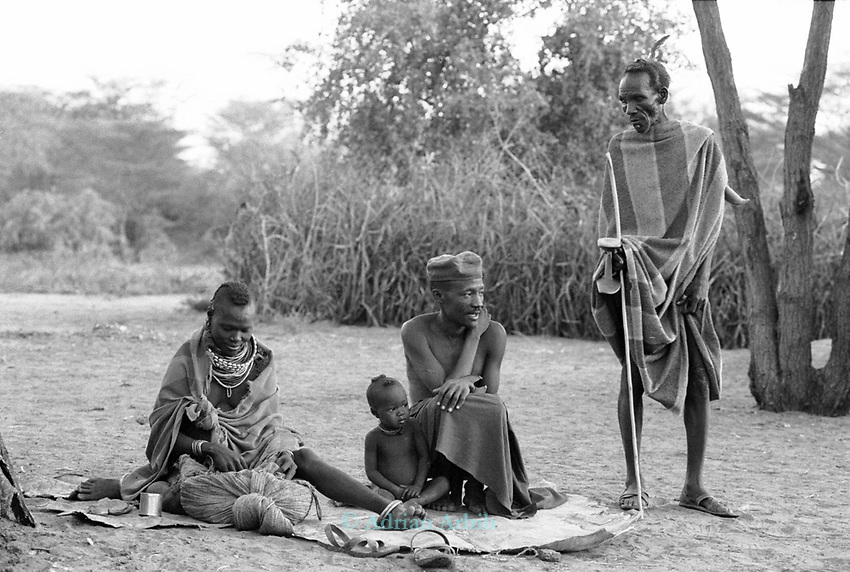 A Turkana family outside their family hut.<br /> Nr Kakuma. Northern Kenya.