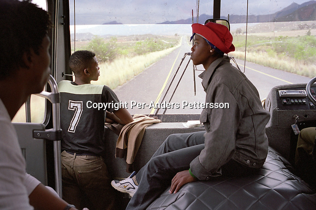 ditrbus00012.Transport, Busses, passengers. Mbulelo Jonas, age 18, Xola Putye, age 17, and Asanda Mabhayi, age 18, ride on a bus during a tour for their dance company on April 7, 2004 in Barrydale outside Cape Town, South Africa. They are some of the about 200 children who dance in a ballet school called Dance For All, which teaches unprivileged children dance after school. Many children are talented and the discipline taught during the dance classes has helped many to improve their concentration in school. .©Per-Anders Pettersson/iAfrika Photos