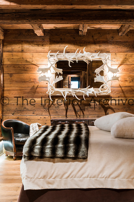 An antler-framed mirror with integrated lights creates an imaginative source of light in the master bedroom