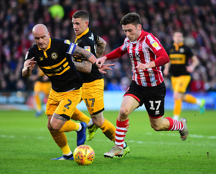 Lincoln City's Shay McCartan gets past Newport County's David Pipe, left, and Scot Bennett<br /> <br /> Photographer Andrew Vaughan/CameraSport<br /> <br /> The EFL Sky Bet League Two - Lincoln City v Newport County - Saturday 22nd December 201 - Sincil Bank - Lincoln<br /> <br /> World Copyright © 2018 CameraSport. All rights reserved. 43 Linden Ave. Countesthorpe. Leicester. England. LE8 5PG - Tel: +44 (0) 116 277 4147 - admin@camerasport.com - www.camerasport.com
