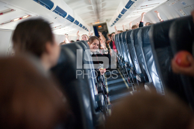 SAN JOSE, CA--Sara James joins in on a cheer for a roll of duct tape rolling down the center aisle during takeoff at Atlantic Aviation en route to Norfolk, VA for the first and second rounds of the 2012 NCAA tournament.
