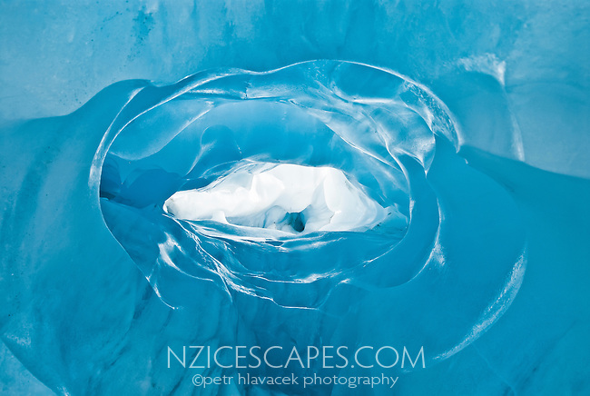 Crawling through brilliantly blue, nicely textured ice cave on Franz Josef Glacier - Westland National Park, West Coast, New Zealand