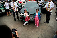 A photographer takes a picture of two girls in front of a new car on display in a public park in Nanjing, China.