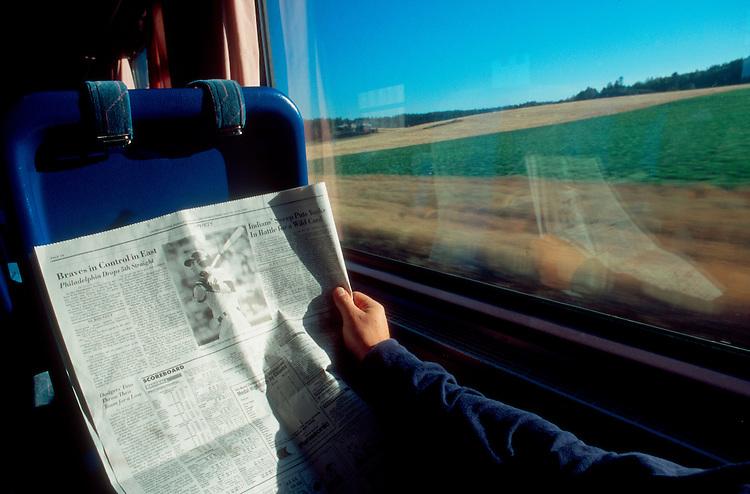Europe, Train travel, Turku, Finland Reading the Herald Tribune on the train,.