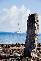 Modern sailing catamaran sails past altar stone and ancient temple Taputapuatea Marae on Raiatea, French Polynesia
