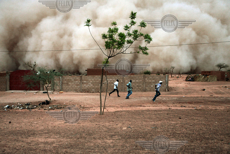 Three men run for shelter from an approaching sand storm on the road between Dosso and Niamey.