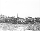 RGS 2-8-0 #74 with caboose #0401 on standard gauge flat cars at Montrose for shipment to Boulder.  A portion of business car &quot;Edna&quot; is on the next car headed for Knott's Berry Farm.<br /> RGS  Montrose, Co  ca. 8/15/1952