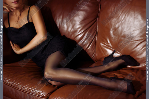 Closeup of legs of a sexy woman lying on a brown leather couch wearing a short black dress, stockings and high heels