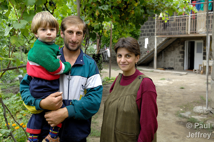 Archil Gogoladze, a Georgian farmer pictured here with his wife and son, received a loan from a church-run microcredit program to purchase cows.
