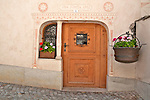 Carved wooden door in the small town of Castasegna, a Swiss town right on the border with Italy in the Bregaglia Valley. This house was originally built in 1566, like most of the houses in the valley, and renovated in 1992. Notice the traditional iron pot by the window filled with flowers, a common sight in the valley towns. The borders around the door are patterns scratched out of the still wet wall, decorative artwork called sgraffiti, traditionally done in two colors and originating in Italy, brought to the Engadin region of Switzerland in the 16th century and is still used today