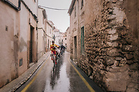 the peloton navigating the narrow slippery Mallorcan streets (during a downpour)<br /> <br /> Trofeo Lloseta - Andratx: 140km<br /> 27th Challenge Ciclista Mallorca