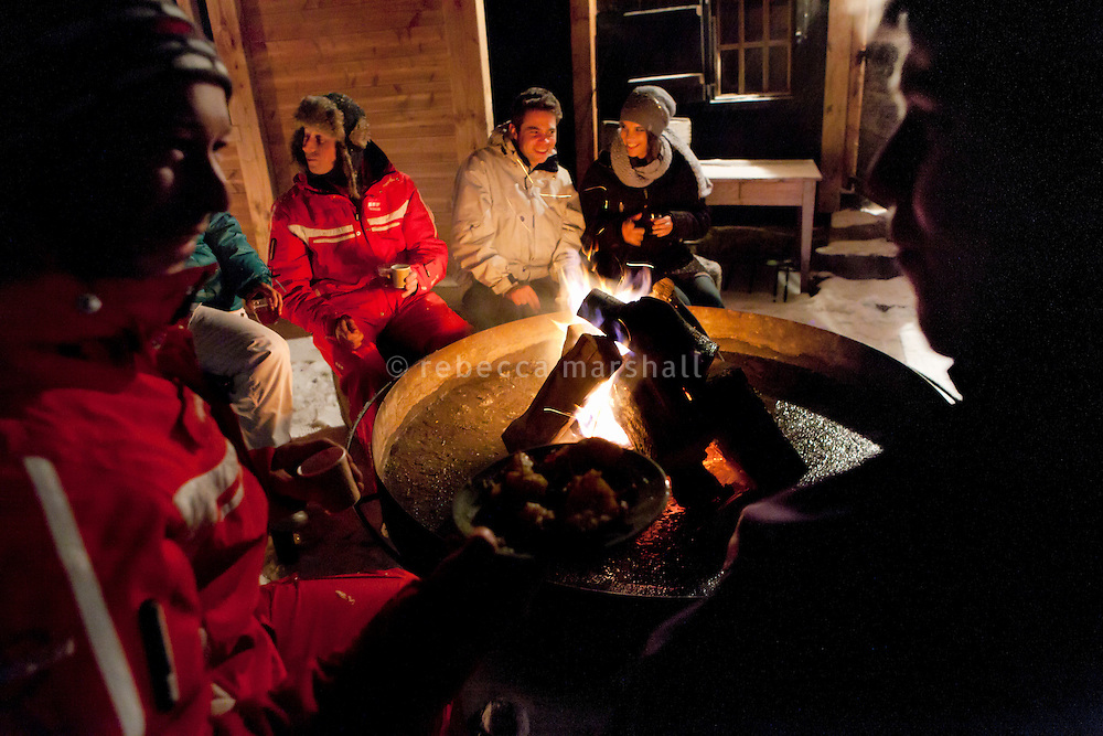 Guests gather round the fire for drinks on the terrace at Chalet Refuge Vé la Marie, La Clusaz, France, 15 February 2012.