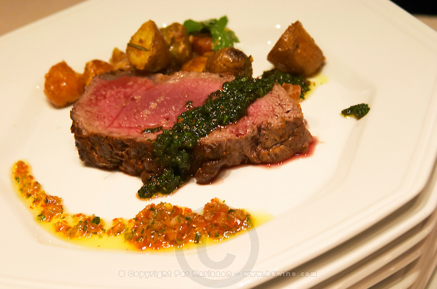 A slice of juicy red roast beef with green herb sauce and yellow tomato and vegetable coulis, roast potatoes. ready to be served. The Dolly Irigoyen - famous chef and TV presenter - private restaurant, Buenos Aires Argentina, South America Espacio Dolli