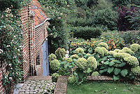 The lush garden is planted in stepped terraces and is full of old-fashioned plants and flowers