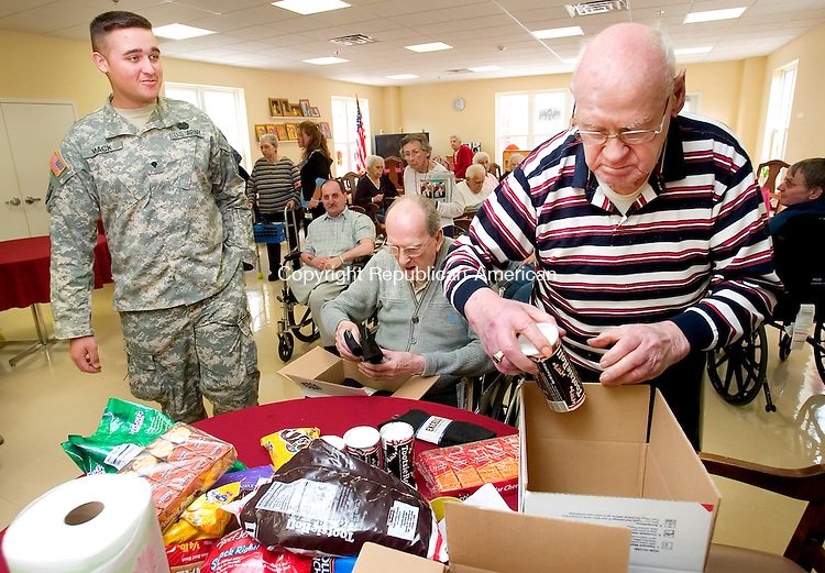 PROSPECT, CT. 05 April 2007-040507SV02--From left, Jeremy Mack, 19, of New Milford, a medic in the Army, packs up supplies and gifts that he will bring back to Iraq with him. World War II vets, Army Corporal Francis Daly and Army Tec. Sgt. Warren Gould help him pack the items at Marathon Health Care in Prospect Thursday.<br /> Steven Valenti Republican-American