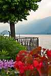 Waterfront walkway with flowers at sunset in Bellagio, Italy