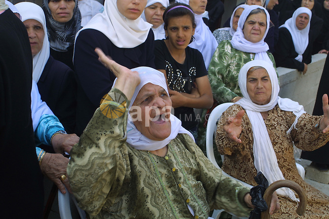 Palestinian relatives of Islamist Hamas movement member Fadi Hamadneh, 22, mourn following his death inside a Palestinian Authority (PA) prison on August 10, 2009 in a West Bank village near Nablus. Security officials said Hamadneh 'committed suicide' while Hamas insisted in a statement he died following 'brutal torture.' Hamadneh was arrested by the PA's intelligence services in June. Palestinian security services in the West Bank are dominated by Fatah, the party of Palestinian president Mahmud Abbas whose forces were ousted from the Gaza Strip when Hamas violently seized the coastal territory in June 2007. Photo by Nedal Shtieh