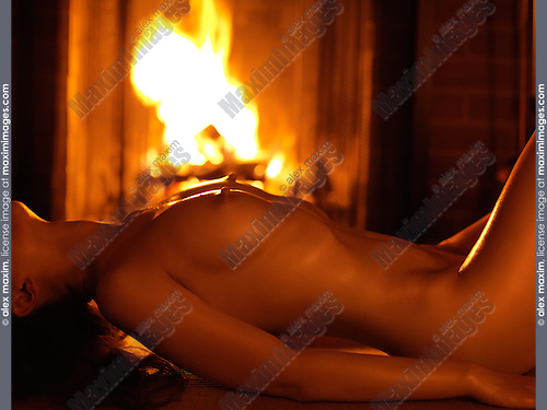 Beautiful woman lying naked in front of a burning fireplace