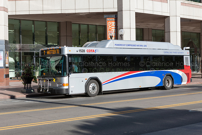 A compressed natural gas (CNG) powered COTA bus waits to load passengers on S High Street in Columbus, Ohio.
