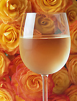 Glass of white wine with yellow roses.