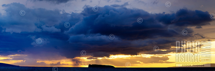 At sunset, sun beams break through gray storm clouds over Molokini Crater, Maui.