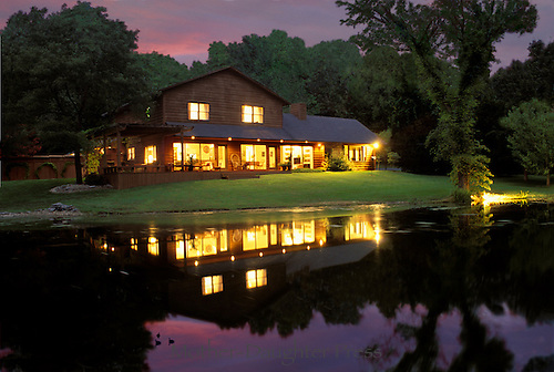 Cedar home brightly lit for evening party with sunset in the background and lake with reflection in front