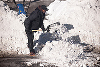 A worker shovels snow in front of a school in the New York neighborhood of Chelsea in the aftermath of Winter Storm Jonas on Sunday, January 24, 2016. The blizzard dumped 26.8 inches onto Central Park making it the second-highest amount since records started in 1869.  (© Richard B. Levine)