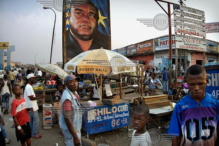 A billboard with the image of the late Laurent Desire Kabila, former president and father of current president Joseph Kabila, in a market place behind a bureau de change stall.