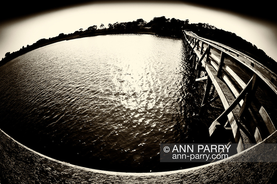 Fisheye lens view of fishing dock in marshland bay at Levy Park and Preserve, Merrick, Long Island, New York, summer 2011. Vintage sepia with vignette