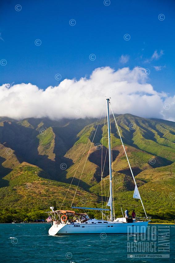 Couple on bow of cruising sailboat at anchor in Kamalo Harbor off Molokai, Hawaii