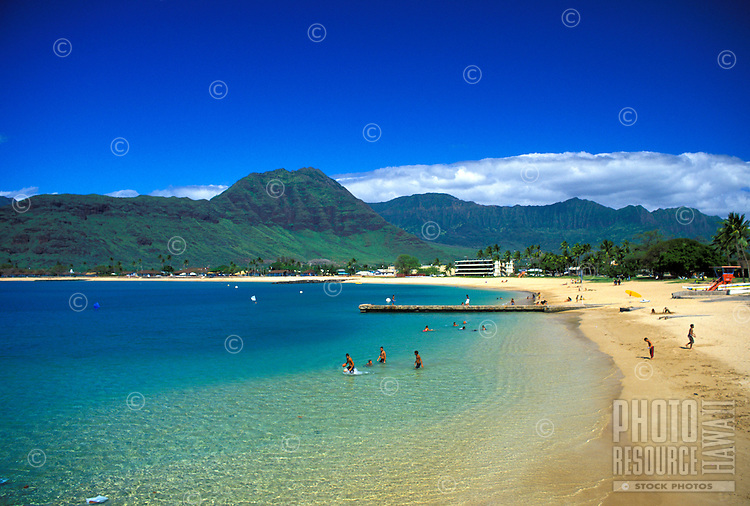 Children swim in the inviting waters of Pokai Bay Beach Park located on Oahu's leeward coast. Waianea mountains in the background
