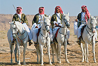 Bedouin men riding horses in the desert inSaudi Arabia.