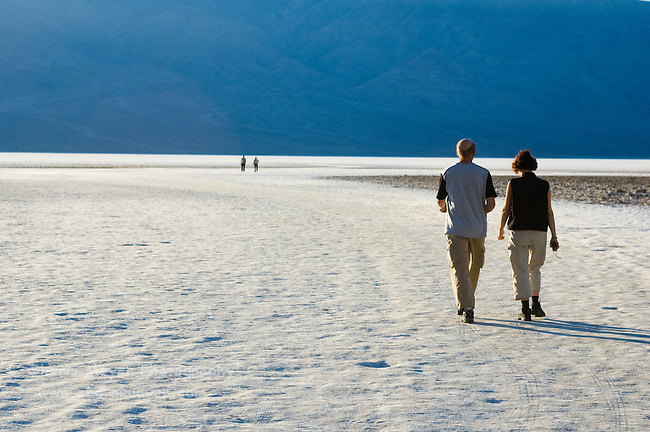 Visitors walking on the salt flats at Badwater Basin, Death Valley National Park, California