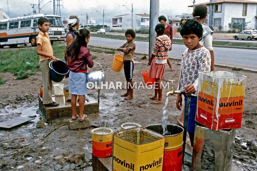 Crianças faveladas recolhendo água em Curitiba, Paraná. 1986. Foto de Juca Martins...
