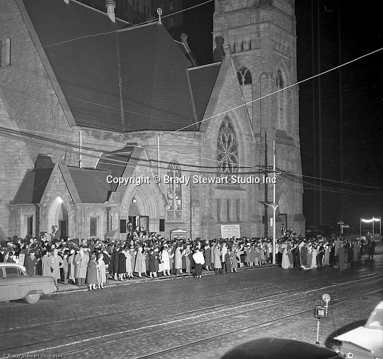 Pittsburgh PA: View of Christmas Services outside the First Luthern Church on Grant Street in Pittsburgh - 1958.  Image of Pastor leading the church choir and faithful in song and prayer.  Many of the group were dressed in period clothing at the time of Jesus's birth.  Brady Stewart Jr took the photography using a large spotlight.