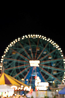 Defocused (Soft Focus) Night View of the Wonder Wheel (landmark ferris wheel) and amusement park at Coney Island, Brooklyn, New York City, New York State, USA