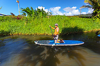 Male stand up paddleboarding on the Hanalei River, Kaua'i