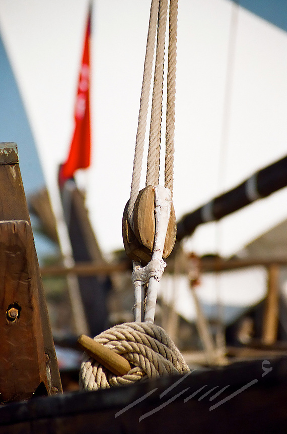 Detail of ropes pulling up the sails of a old wooden ship. The background shows the old flag of Kuwait, back in time where Kuwaiti people used to use these ships to cross the Indian Ocean for trading and pealing.