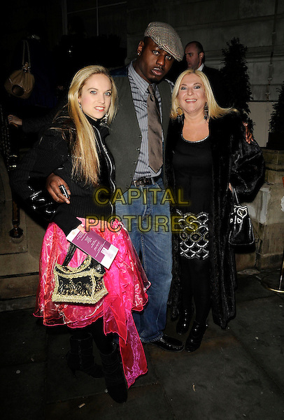 "VANESSA FELTZ, ALLEGRA KURER & BEN OFOEDU.Attending the book launch party for ""In Bed With..."" at the Artesian at The Langham Hotel, Portland Place, London, England, February 11th 2009..full length family fiance daughter mother couple black fur coat pink skirt cap hat tie green waistcoat jeans .CAP/CAN.©Can Nguyen/Capital Pictures"