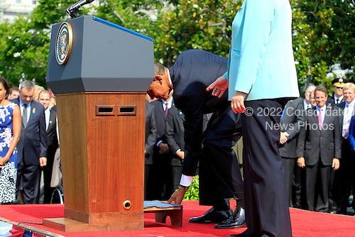 United States President Barack Obama, left, adjusts a stool at the lectern for German Chancellor Angela Merkel before she speaks during a welcoming ceremony on the South Lawn of the White House in Washington, D.C., U.S., on Tuesday, June 7, 2011. .Credit: Andrew Harrer / Pool via CNP